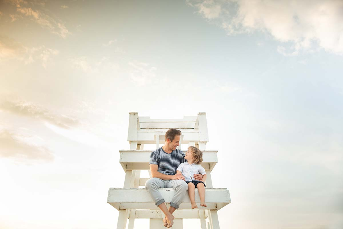 Father and his young son sitting on a lifeguard tower at a beach near Greenwich, CT.