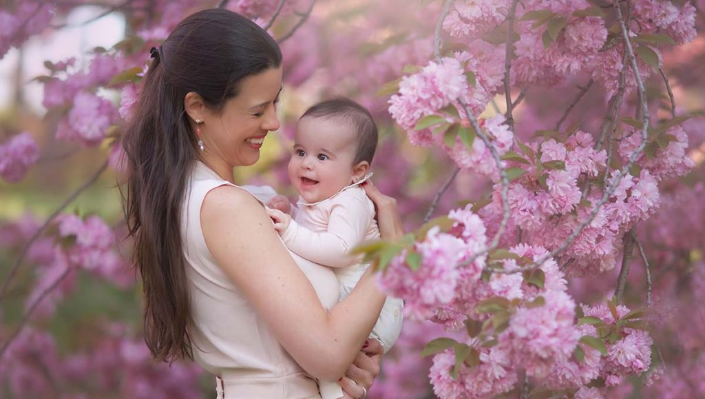 Photo shoot of a mother and her baby girl amidst blooming cherry blossom trees
