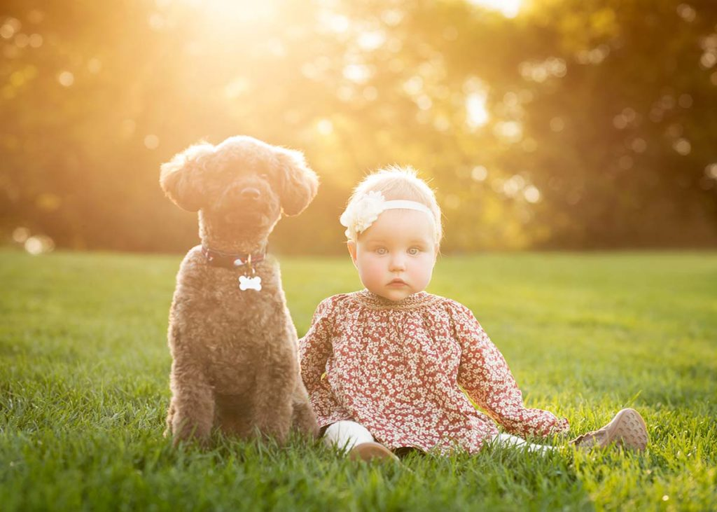 A young girl and her dog sitting in grass during sunset