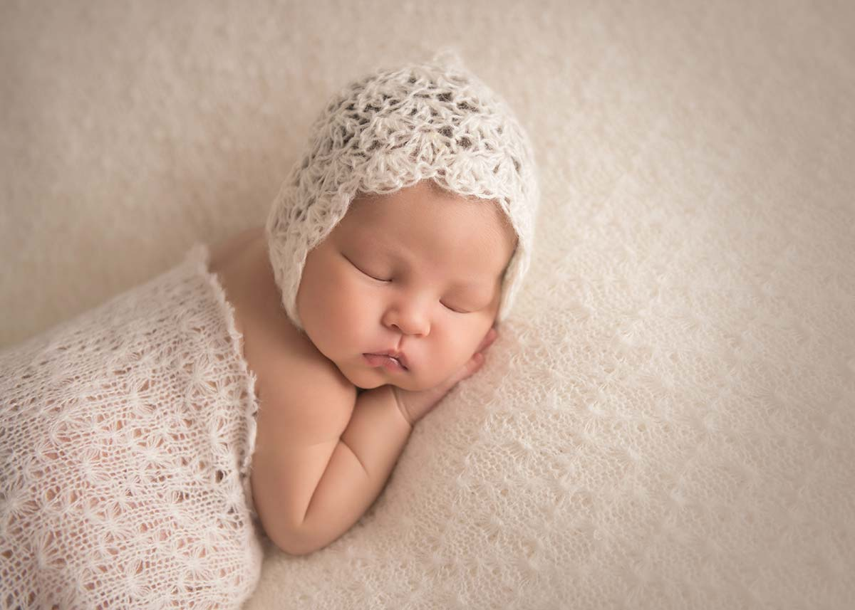 Sleeping baby in a knit blanket and a beautiful bonnet