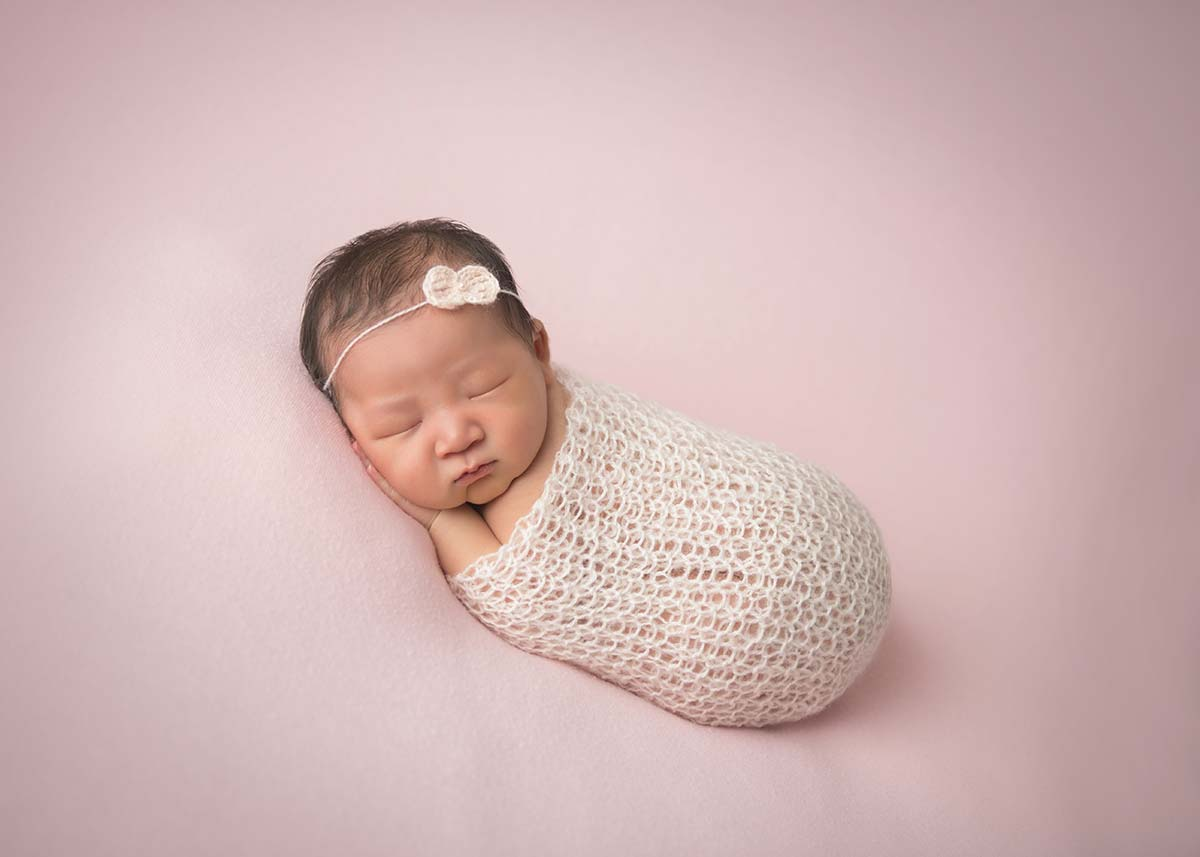 Newborn baby sleeping happily on a blanket in this precious newborn photo