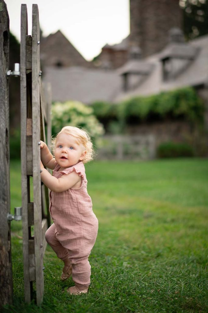 Baby in overalls climbing a wooden gate at a Connecticut farm