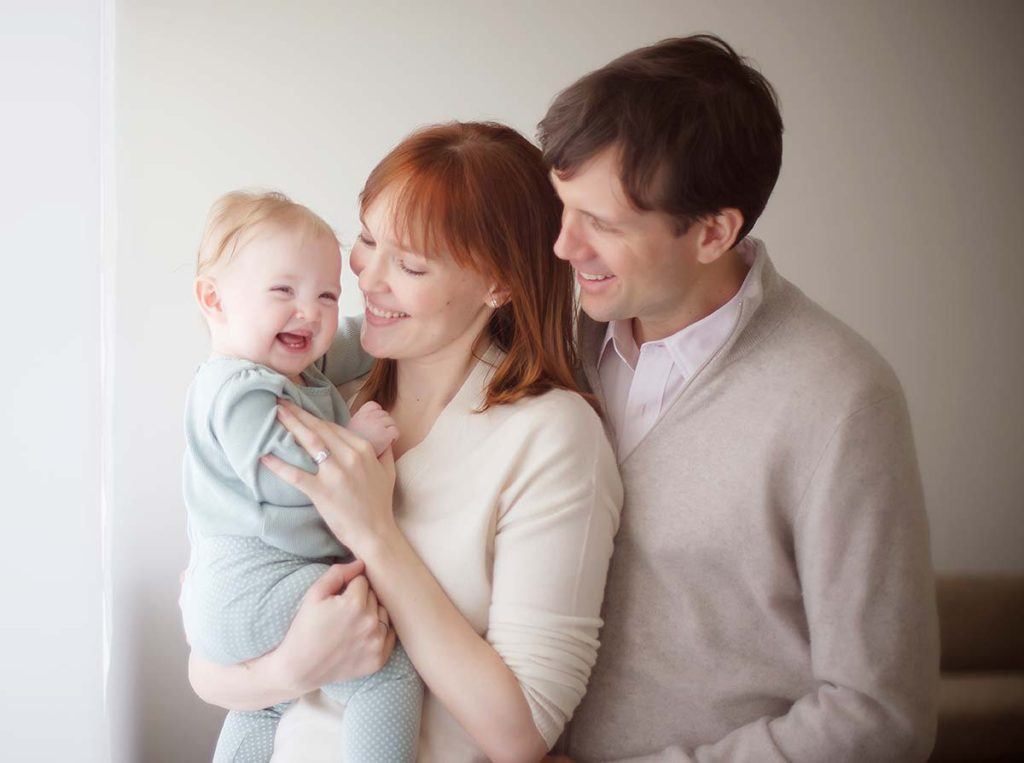 Beautiful family holding a smiling baby in Scarsdale NY