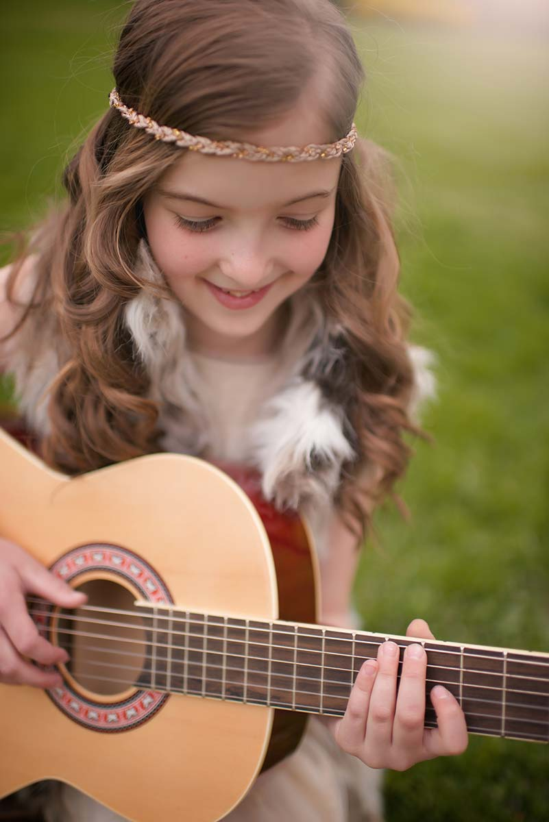 Beautiful girl in a fur vest and a headband playing a guitar