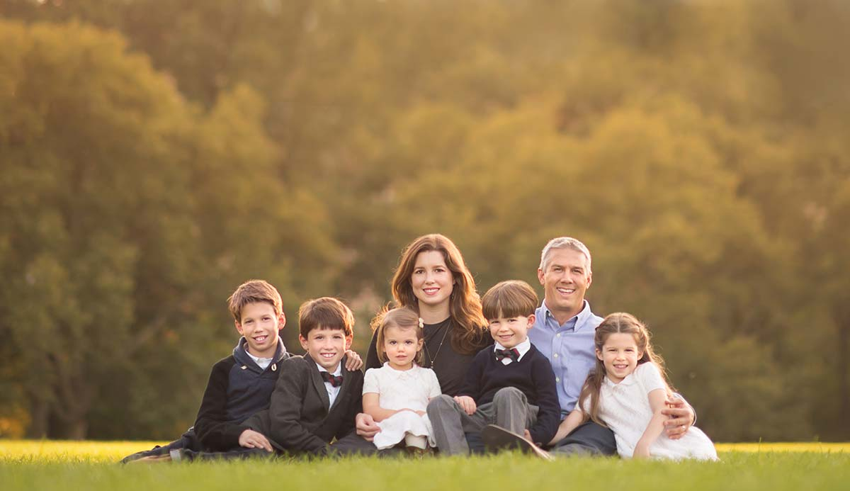 A family with five children sitting in grass and posing for this timeless family photograph taken in western Connecticut