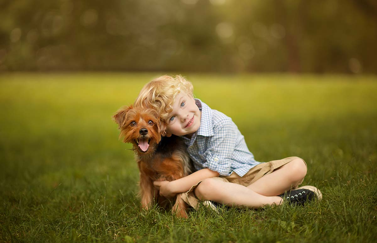 Handsome boy with blonde hair cuddling his dog in a park