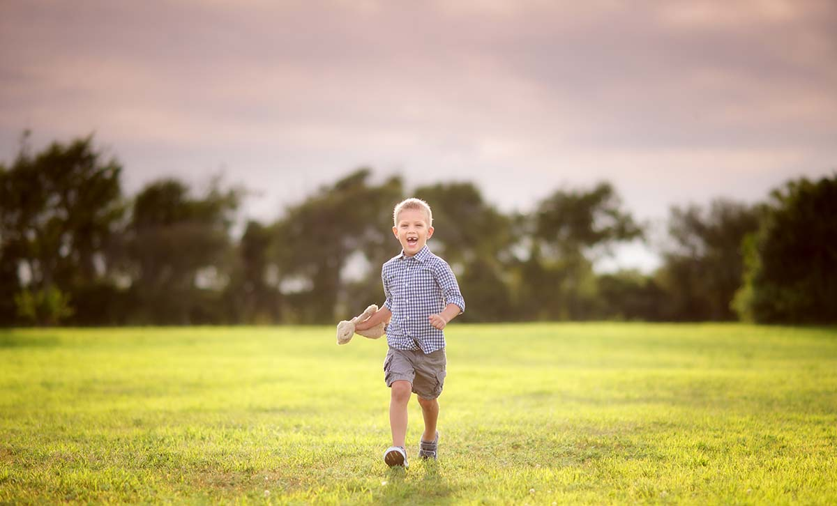 Happy boy in shorts running through a field in Stamford CT while holding his stuffed animal