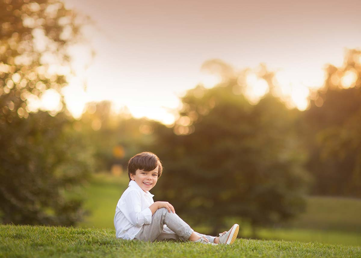 Young boy in a white shirt sitting in a park during sunset