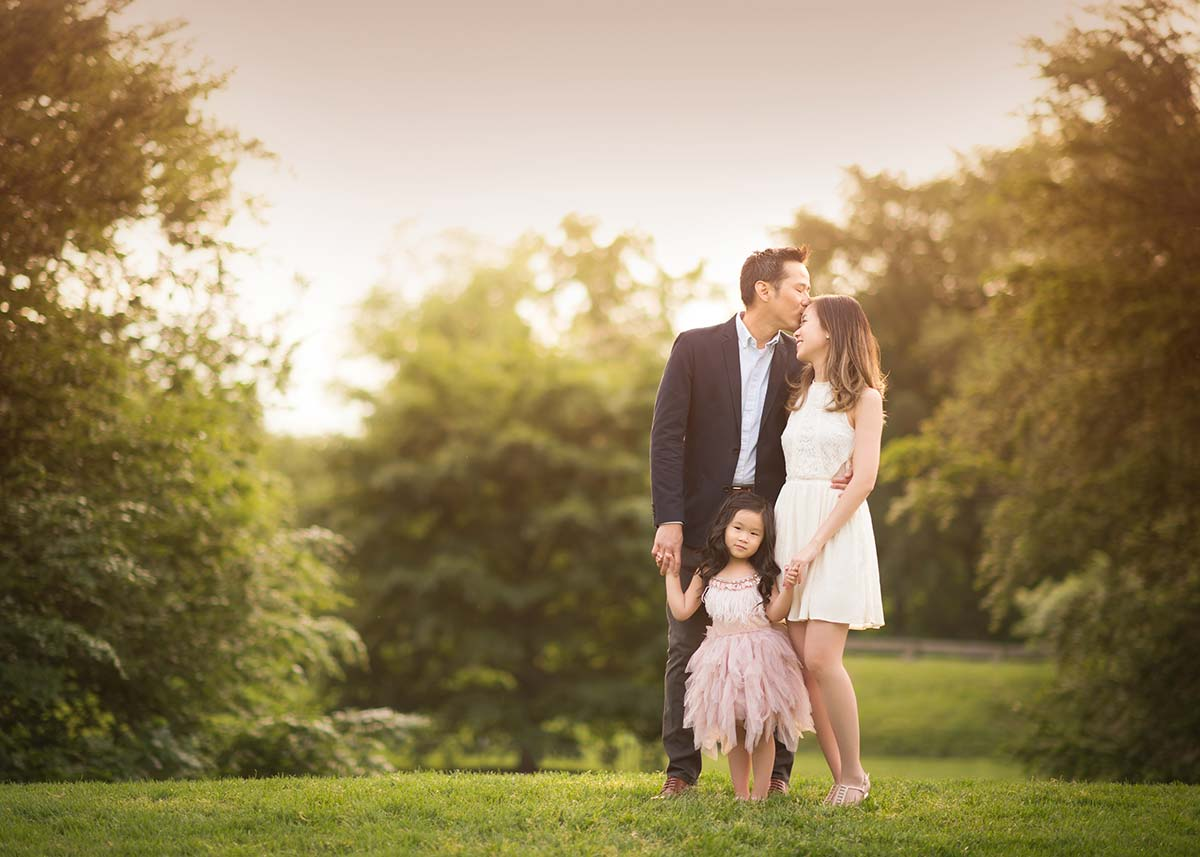 A family from Bronxville, NY posing for a family photograph in a park setting during sunset.