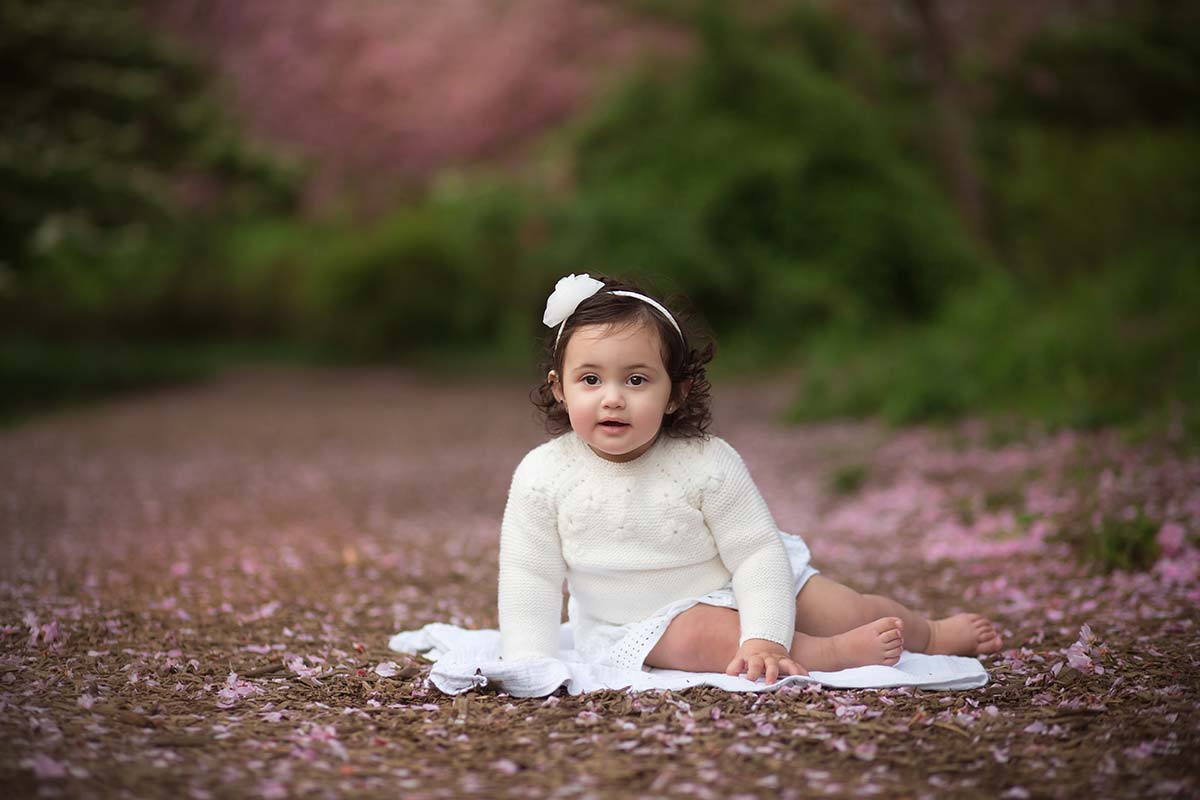 Cute baby girl sitting amidst cherry blossoms in Connecticut