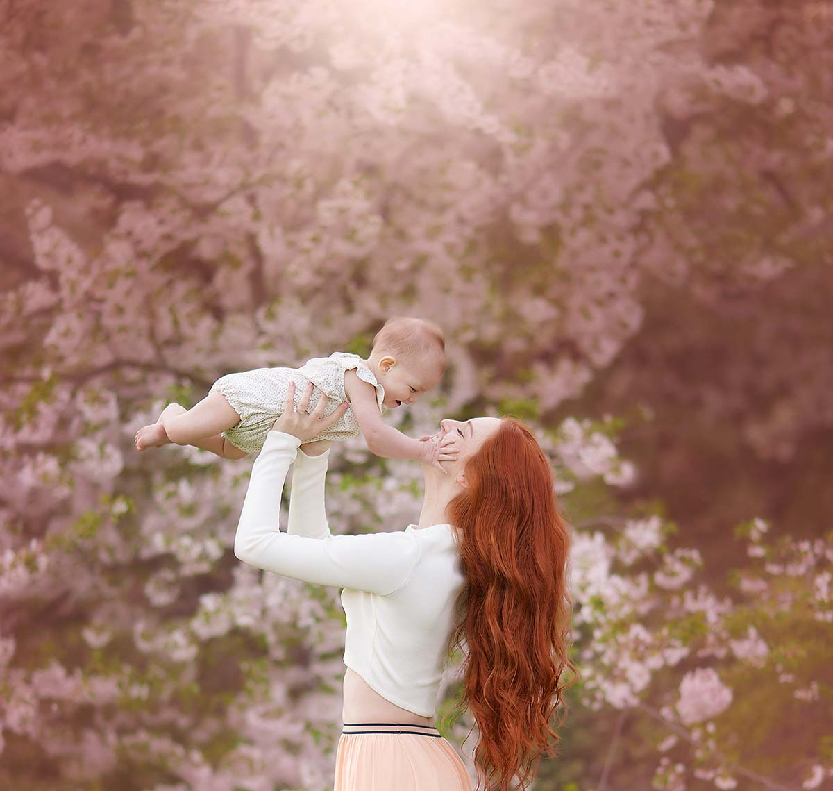 Mother with red hair holding her pretty baby amidst cherry blossoms