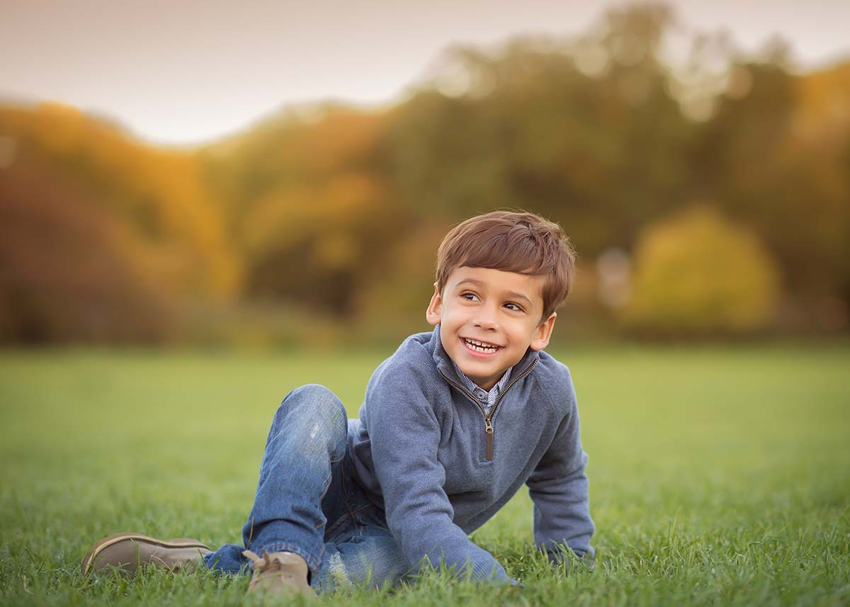 Young boy crawling in grass and smiling