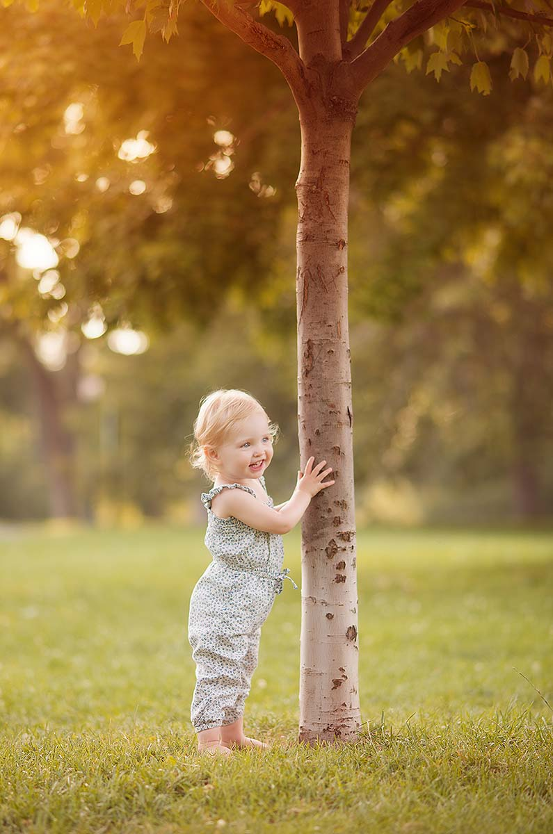 Cute baby girl holding a tree trunk