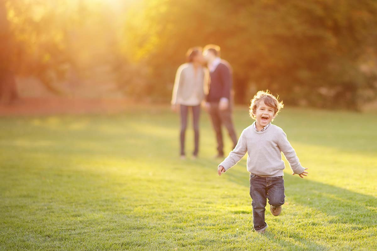 A happy boy running in sunset with his parents kissing in the background at a park in Greenwich CT