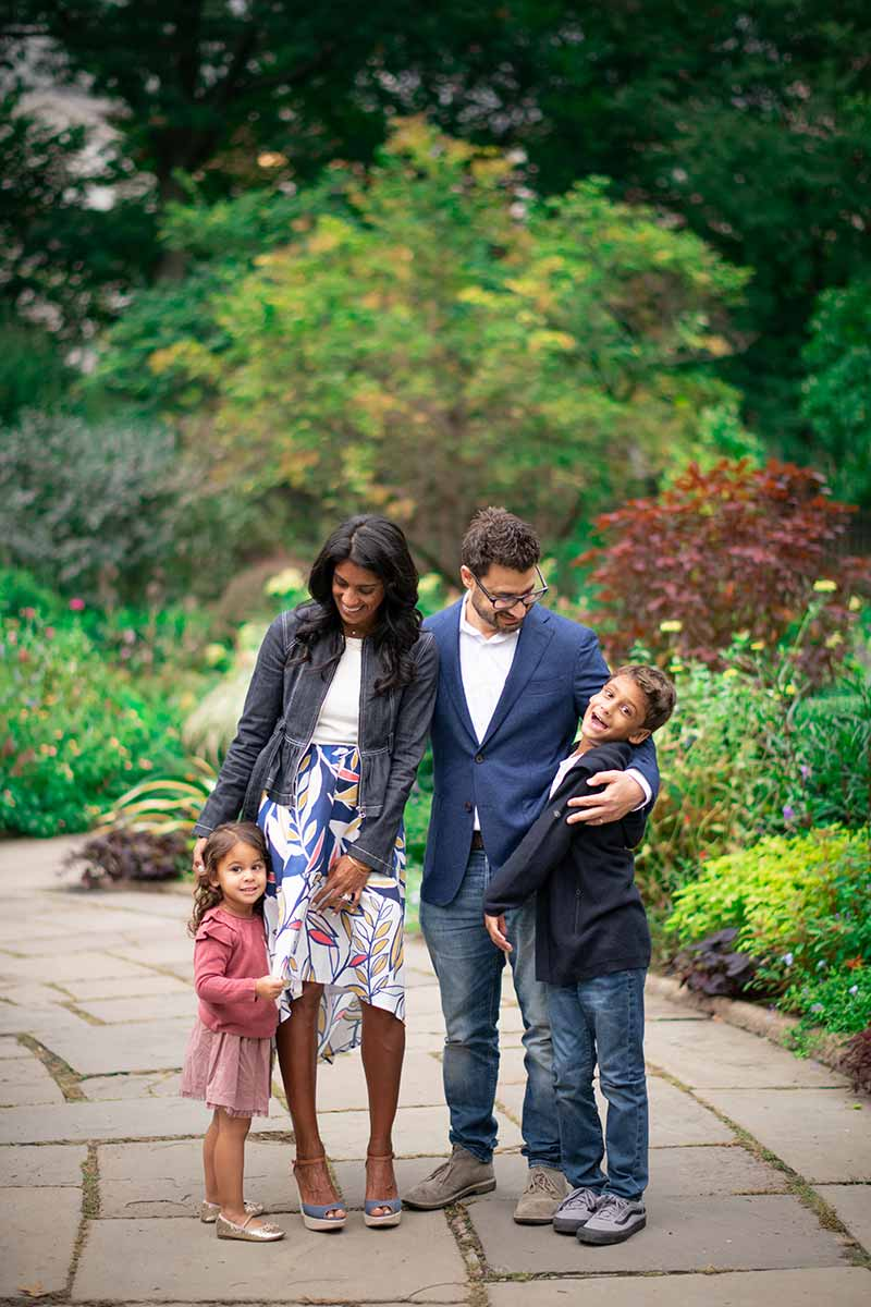 Children laughing with their parents at a garden in this stunning family photo taken in Westchester county NY