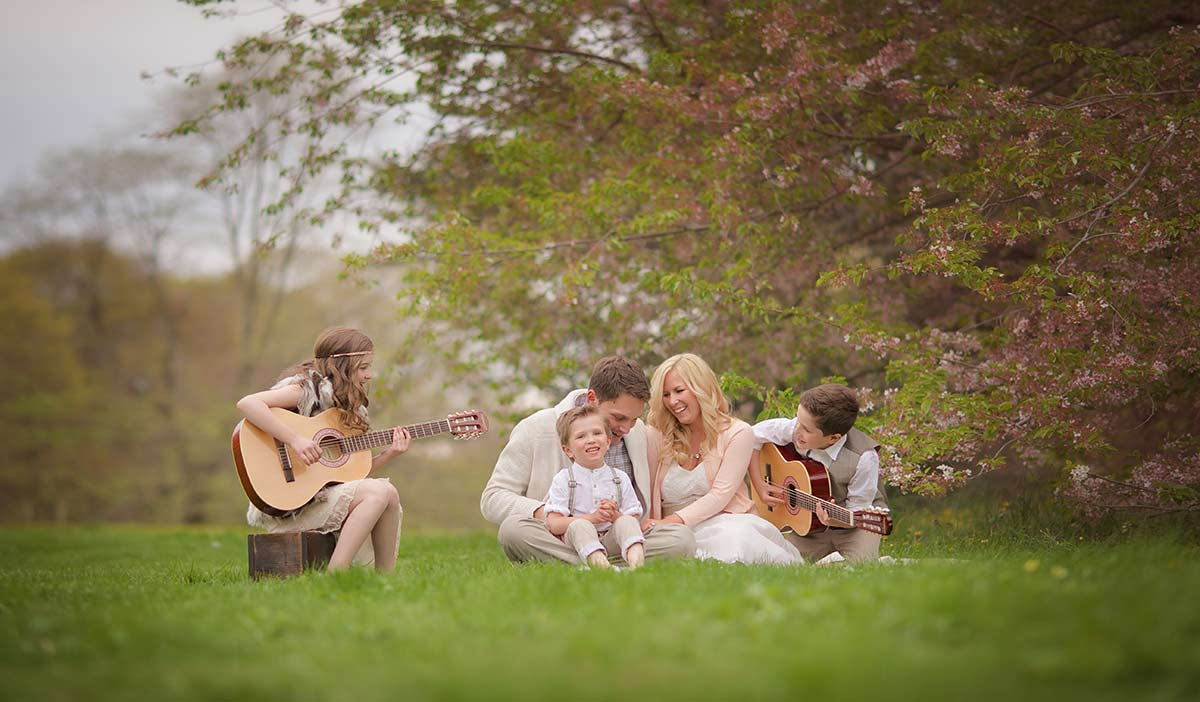 A stylish family sharing a picnic in a park with children playing guitars in a park in Connecticut.