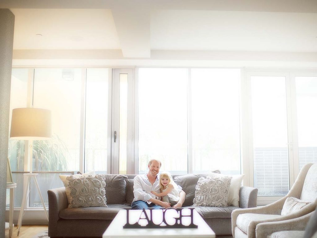 Happy father cuddling his daughter on a couch in their Scarsdale New York home