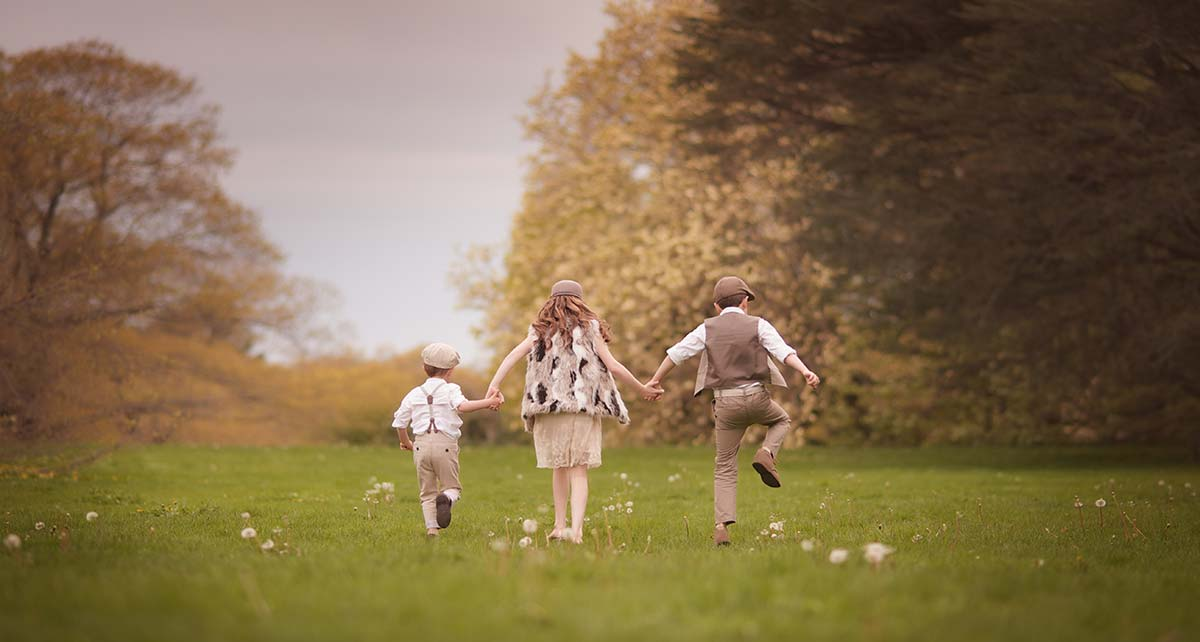 A candid moment shared amongst three young siblings in a meadow near Darien, Connecticut.