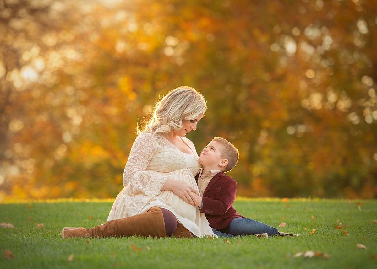 A pregnant mother and her son sitting in grass during the fall season in this Scarsdale NY park