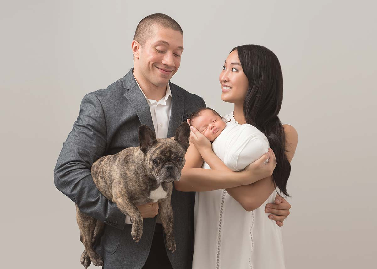 A candid moment shared amongst parents along with their infant baby and family pet in this beautiful photo captured by a newborn photographer in Scarsdale, NY.
