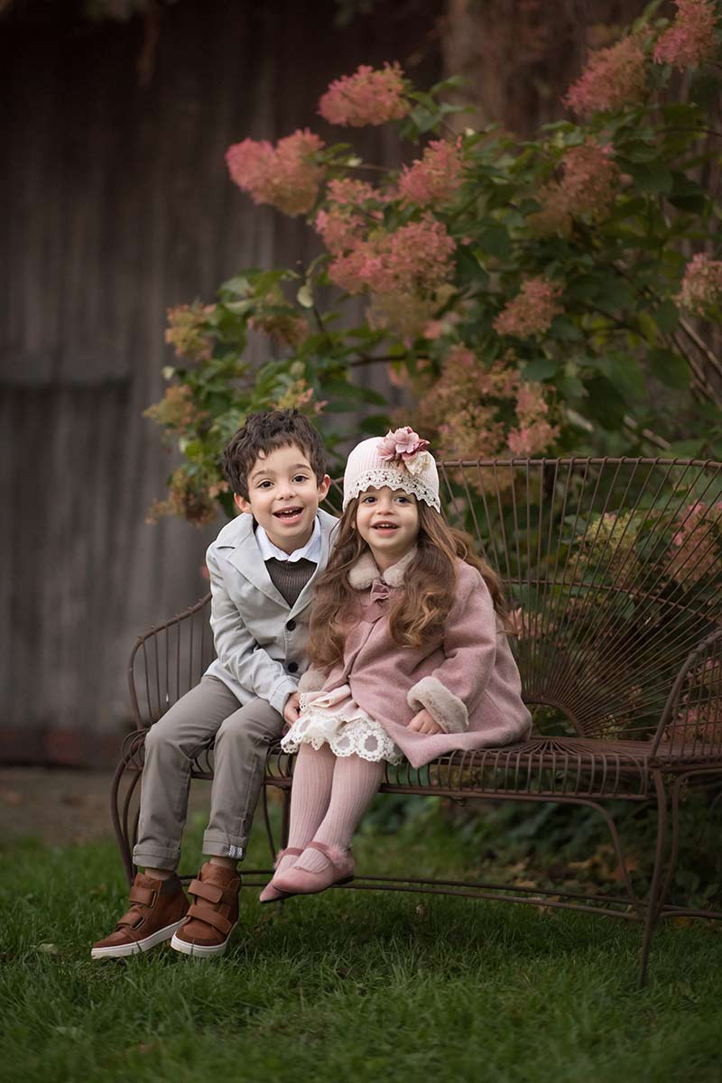 Two beautifully dressed children smiling on a wrought iron bench in a flower garden in Armonk, NY.