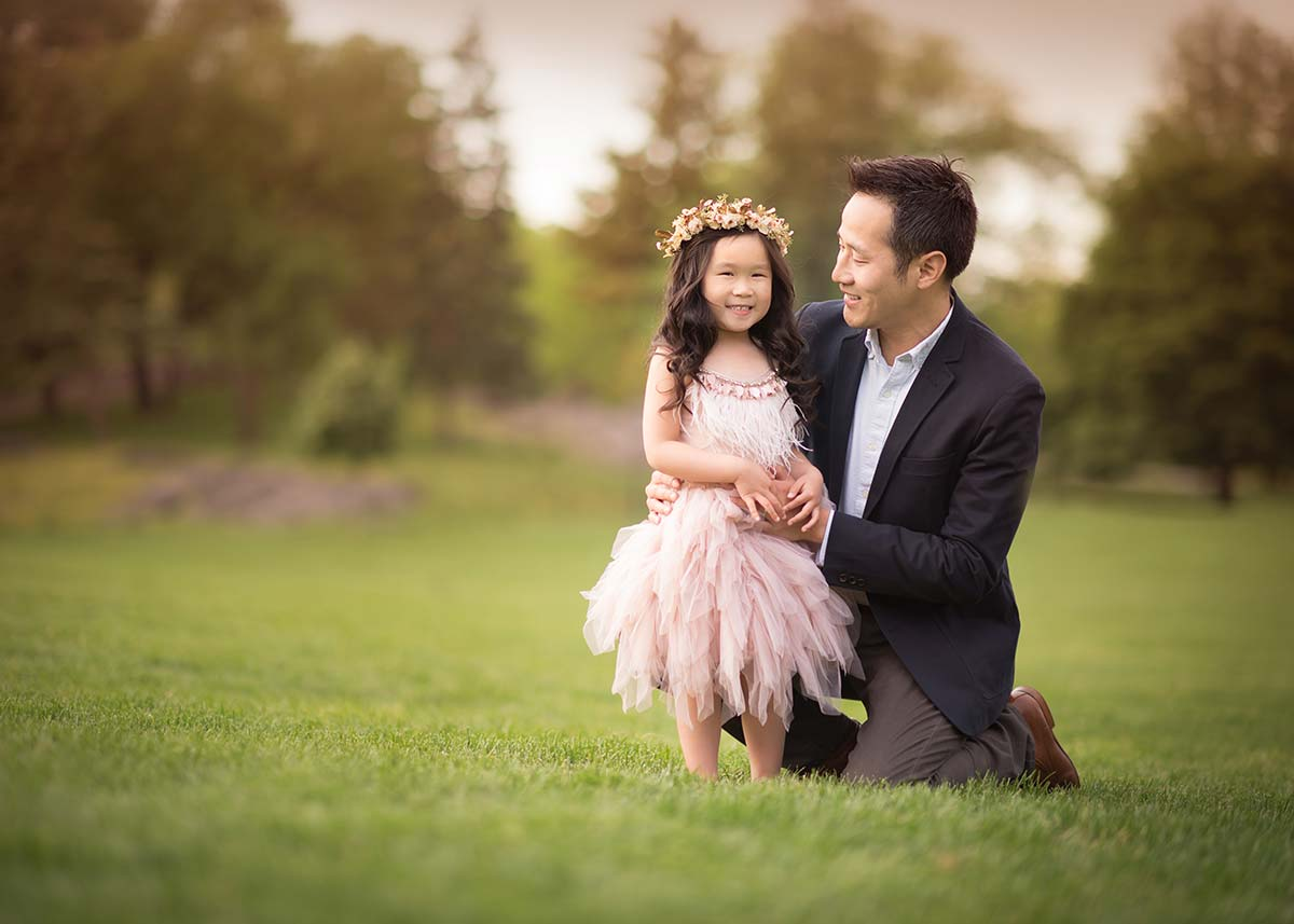A proud father holding the hand of his young daughter wearing a tutu dress in a garden near Rye, NY.