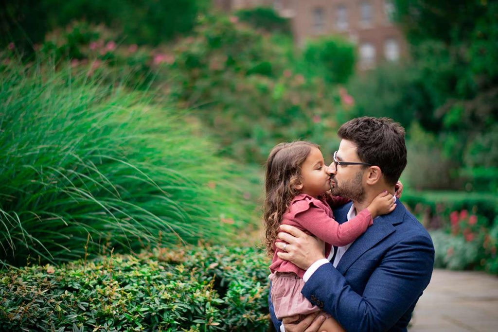 Dad kissing his baby daughter in botanical gardens in Connecticut