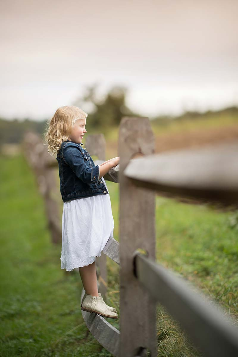 Priceless baby photo of a girl standing on a farm fence