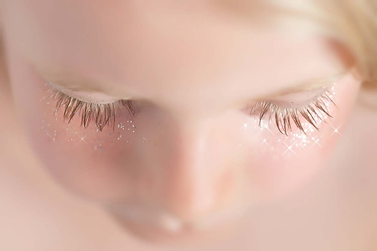 Closeup of girl's eyelashes with sparkles
