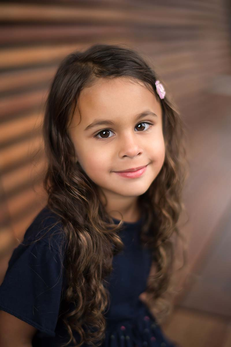 Girl with dark eyes and brown hair looking happily into the camera and smiling in this beautiful child photo