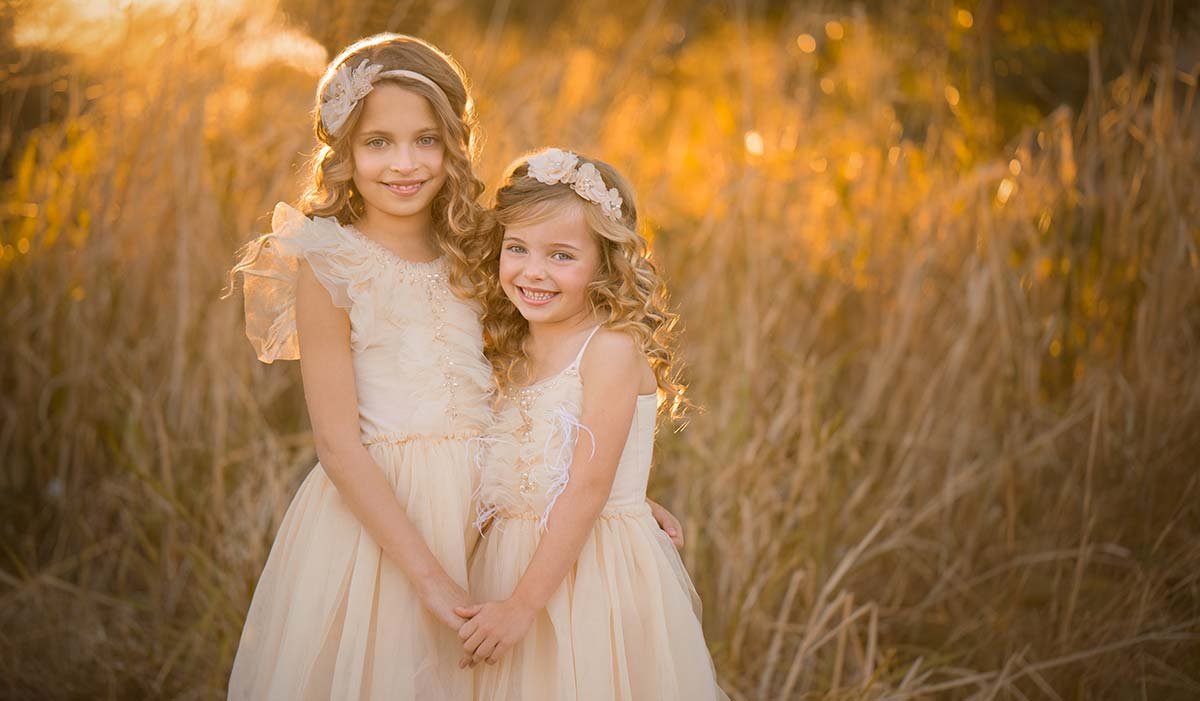 Two beautiful girls with blonde hair and matching dresses pose for a photo during the golden hour