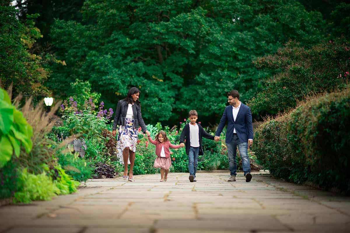 Family with children holding hands and walking in a botanical garden in Rye, NY