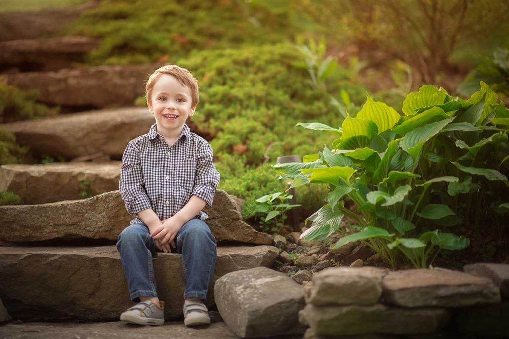 Lifestyle photoshoot in Armonk NY of a cute boy sitting in his backyard