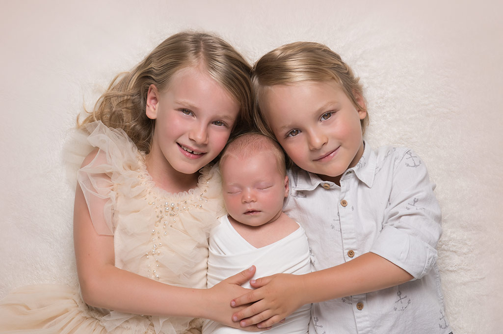 Brother and sister holding their newborn baby