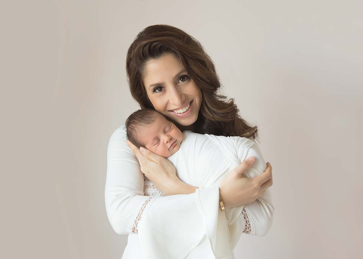 Smiling mother holding her baby in this newborn photo