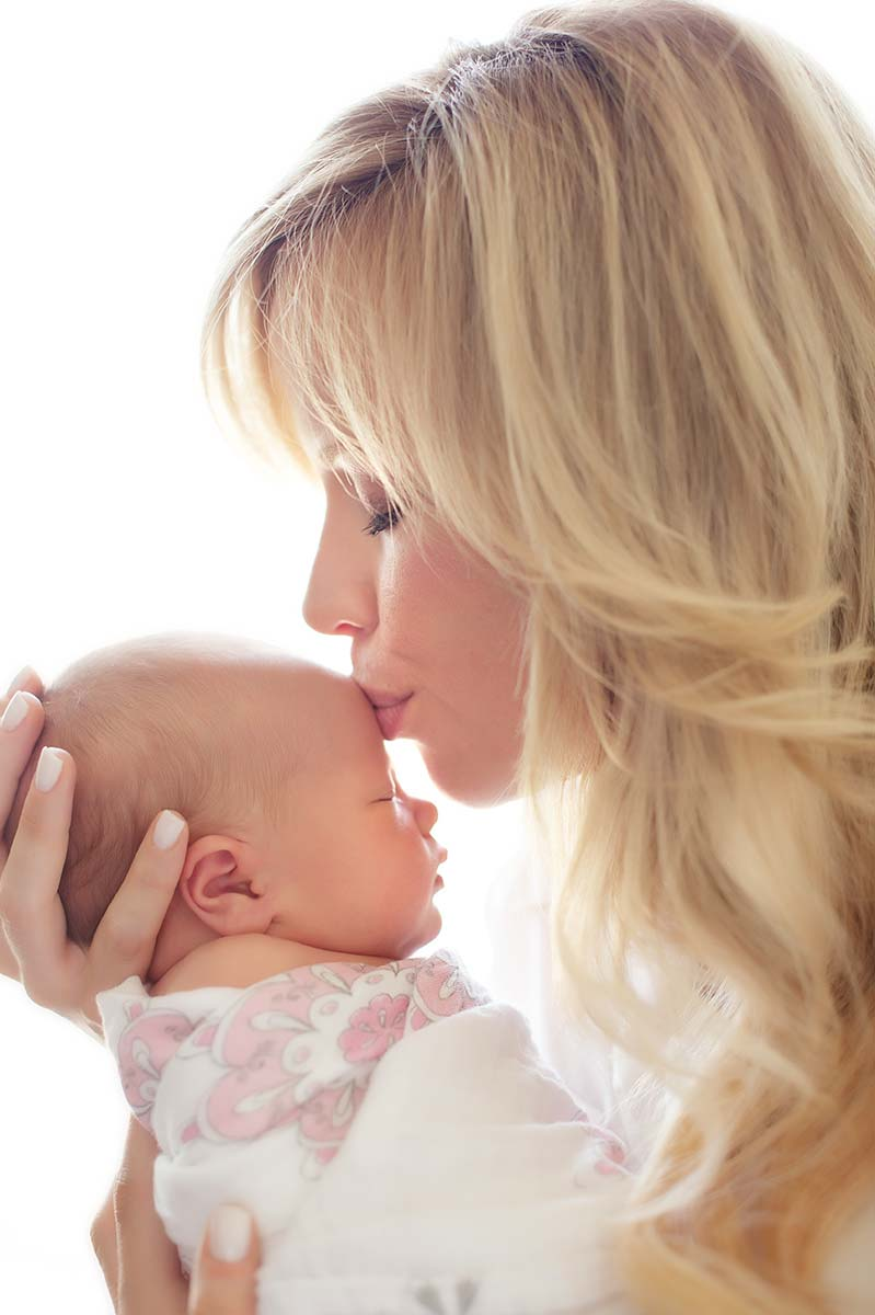 Attractive blonde woman kissing her baby in this photograph taken in Westchester County, NY.
