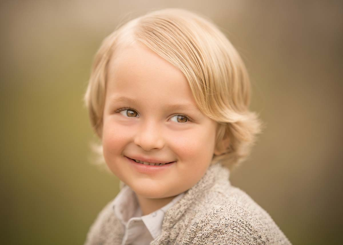 Beautiful young boy with long blonde hair smiling for the baby photographer in Connecticut