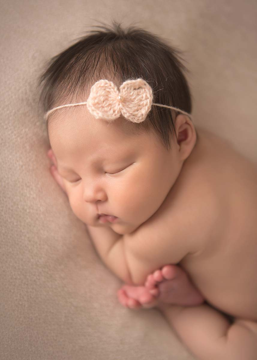 Infant baby with a headband and her feet curled up posing for the photographer