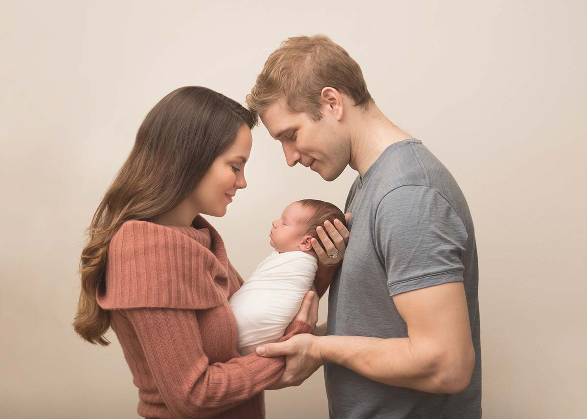 Joyous parents holding their infant for a photo