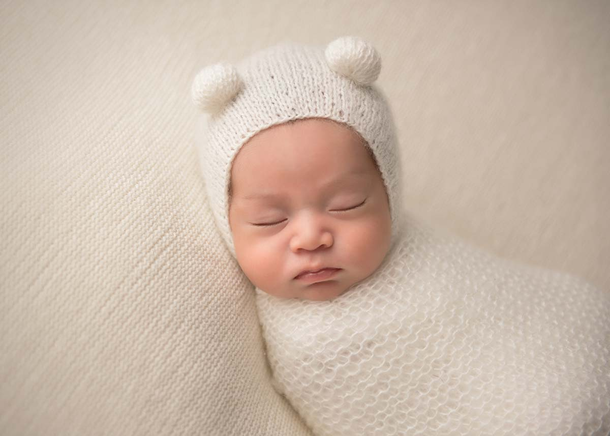 Teddy bear hat worn by a sleeping newborn at a photo studio in Westchester County NY