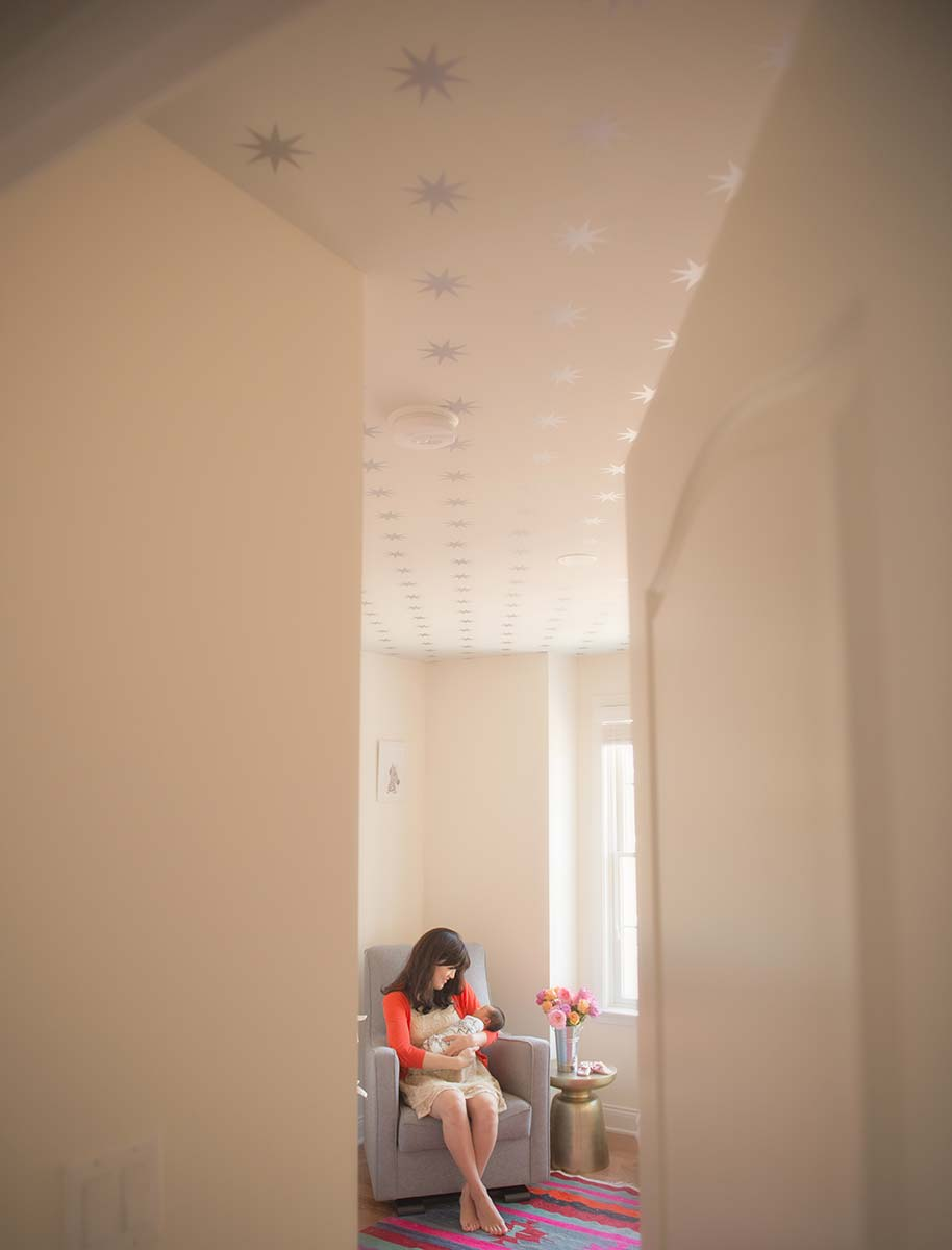 Twinkle stars line the ceiling of this Stamford CT nursery where a mother enjoys a bonding moment with her newborn baby.