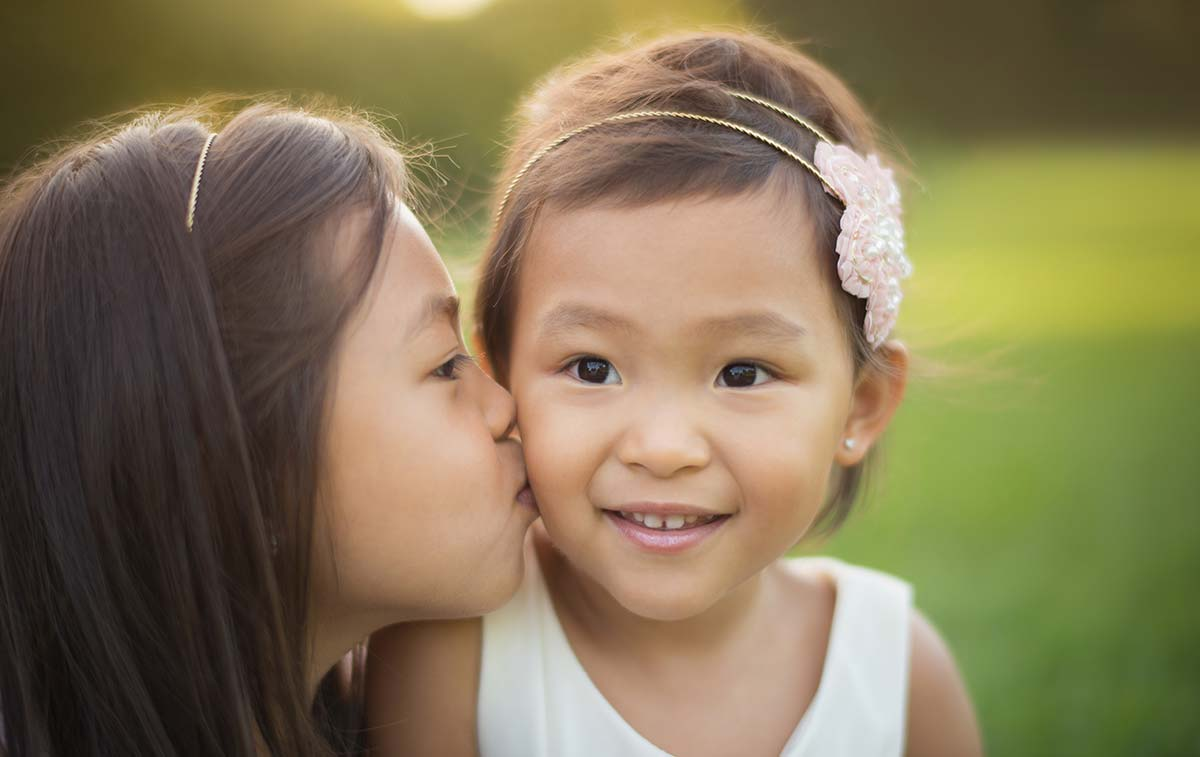 Two beautiful baby sisters kissing in this lifestyle baby photo