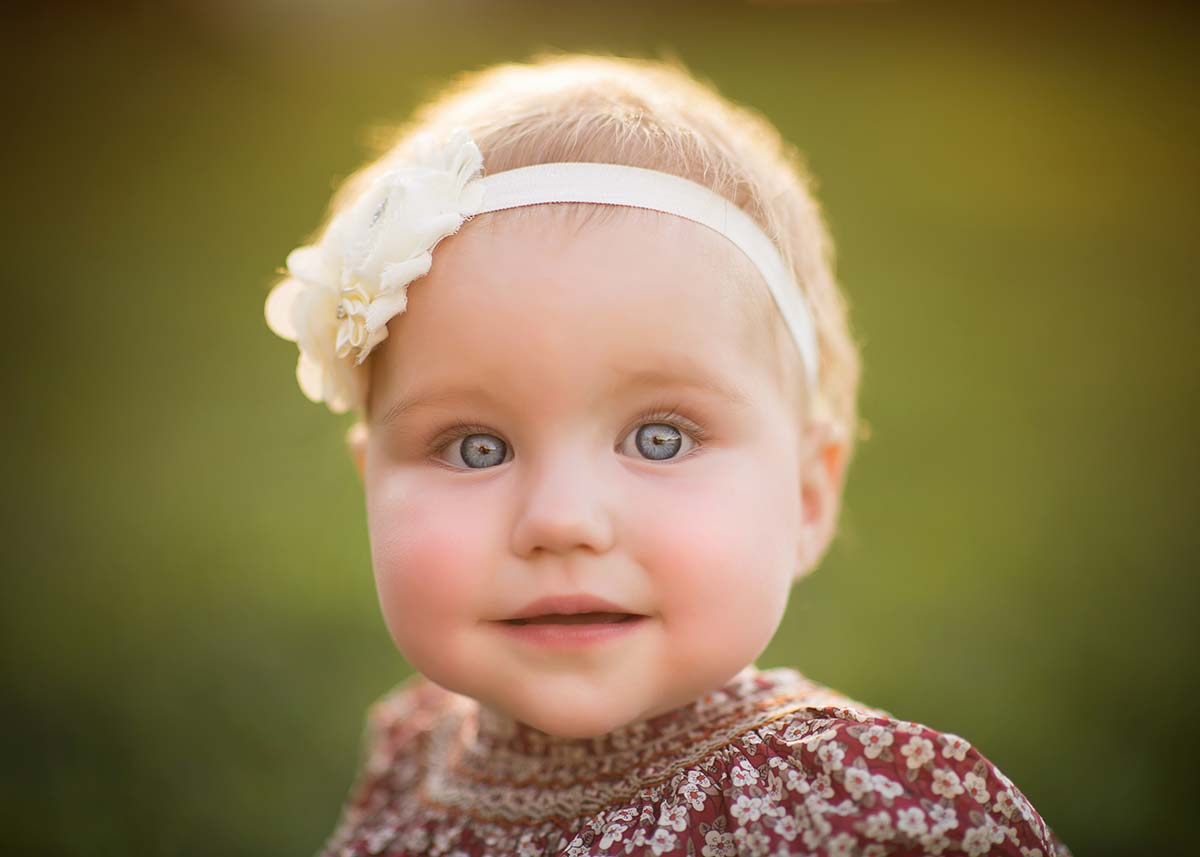 Baby girl with blue eyes and a headband smiles for the camera