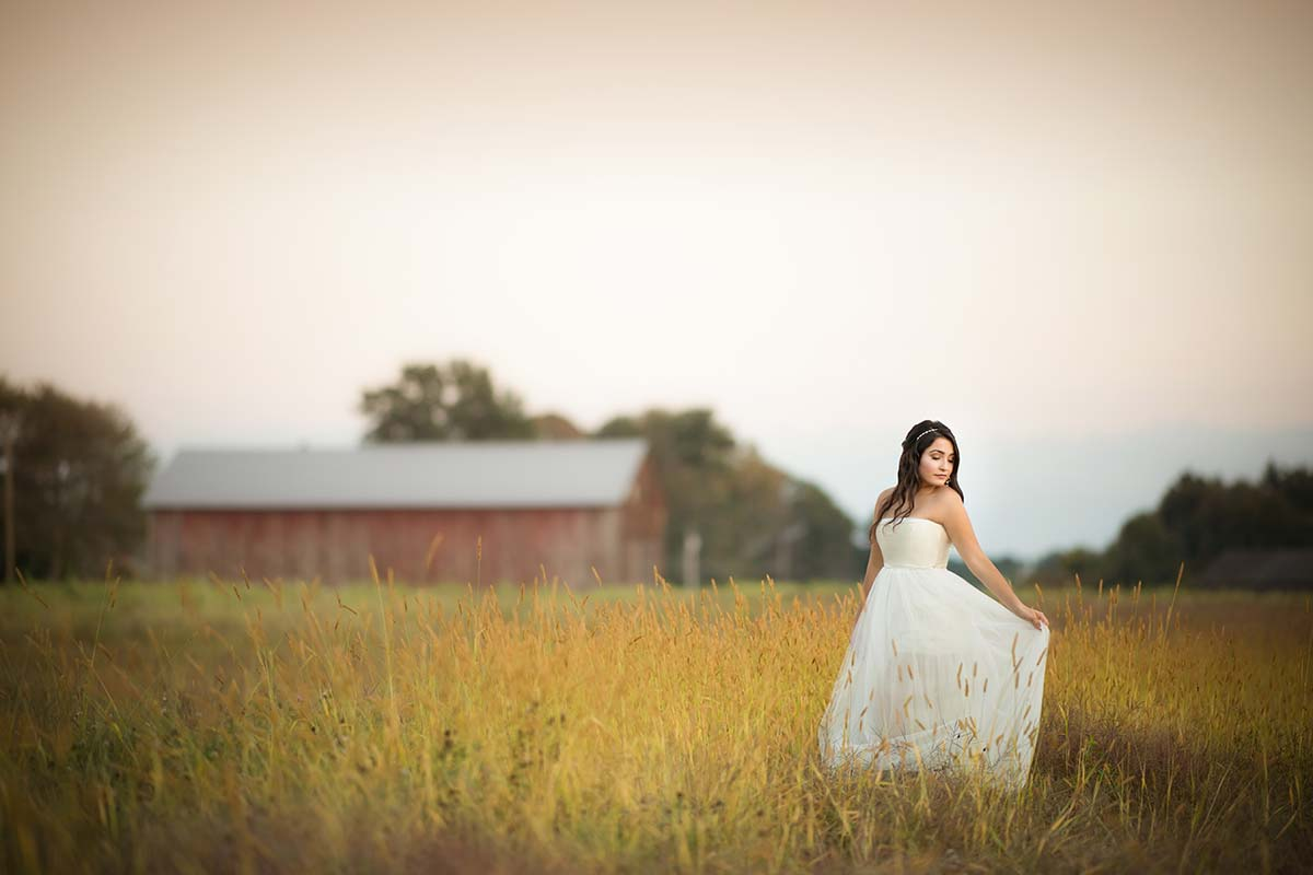 A girl in a long white dress standing in a field of grass near a farm in Westchester county, NY.