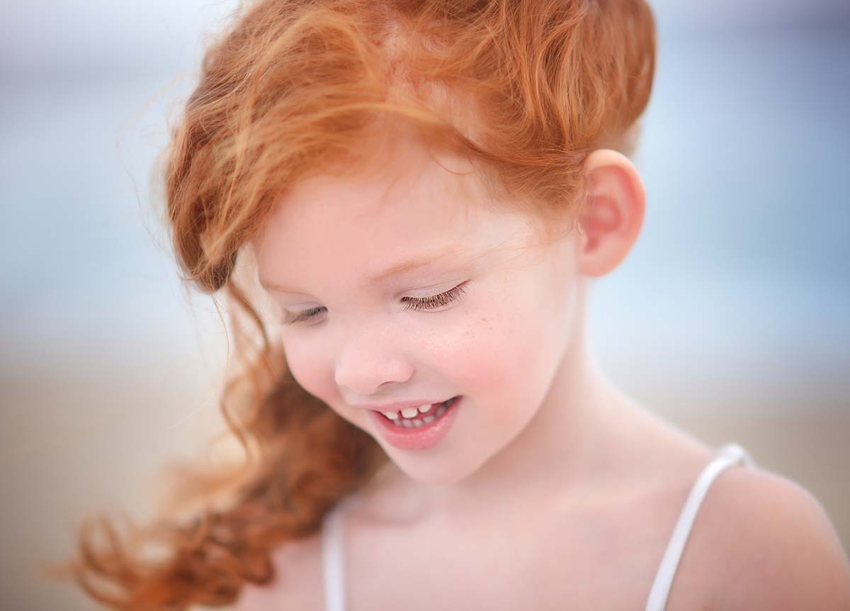 Beautiful redhead girl smiling at a beach setting near Greenwich, CT.