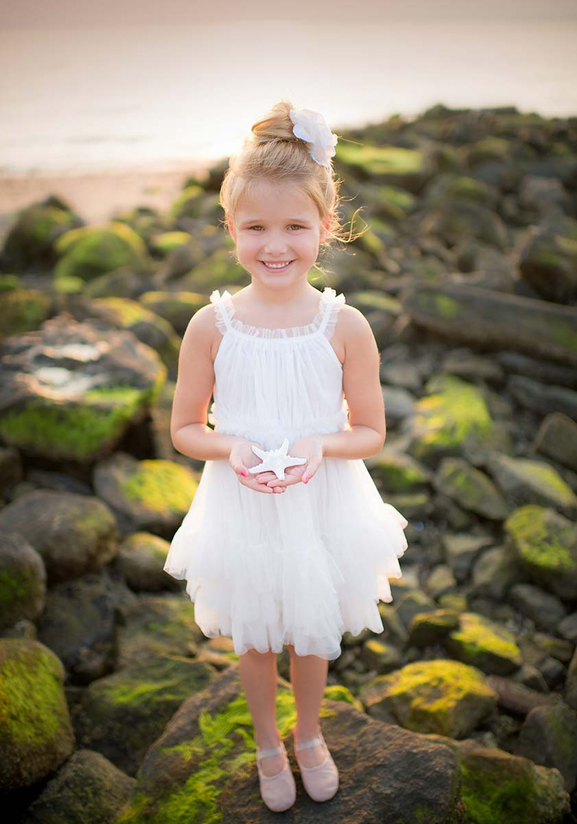 Girl in a tutu holding a starfish at a beach