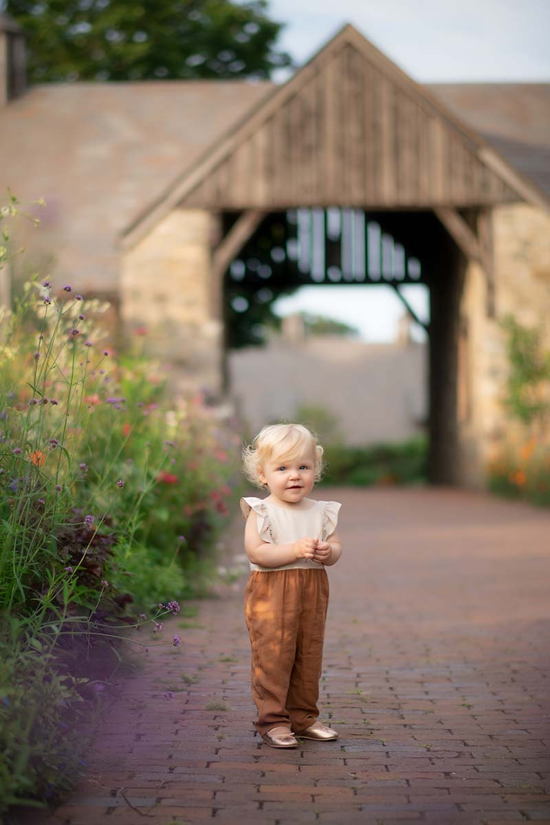 Happy baby with blonde hair standing on a brick path at a farm near Rye, NY.