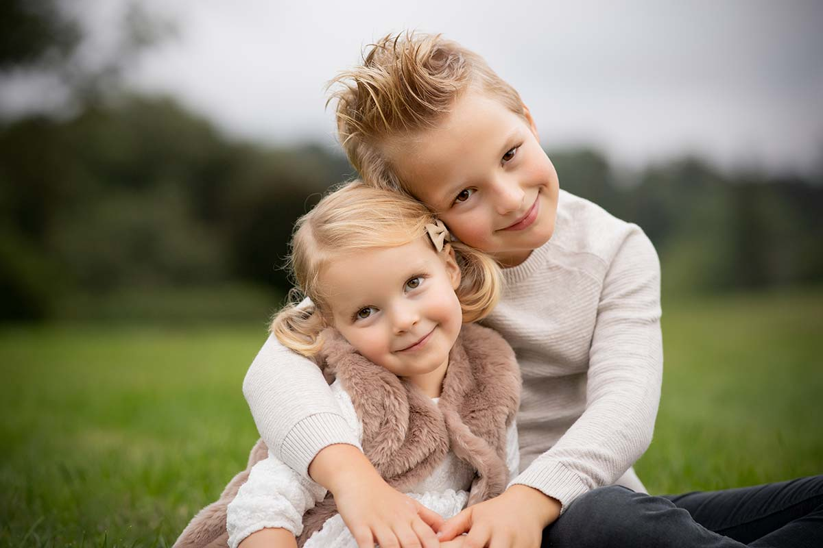 Photo of two siblings hugging on a grass field in Westchester County NY as captured by a baby photographer.
