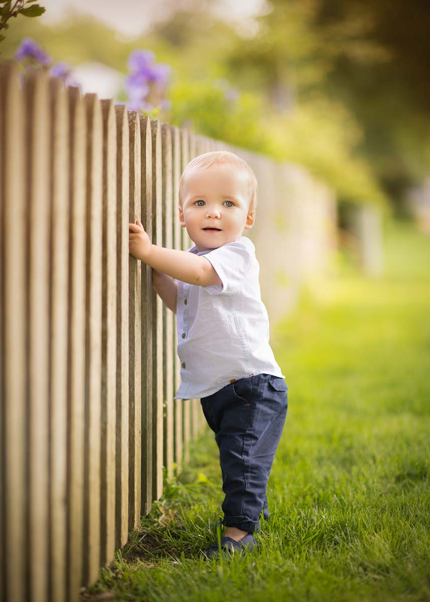 Wooden picket fence held by a toddler boy