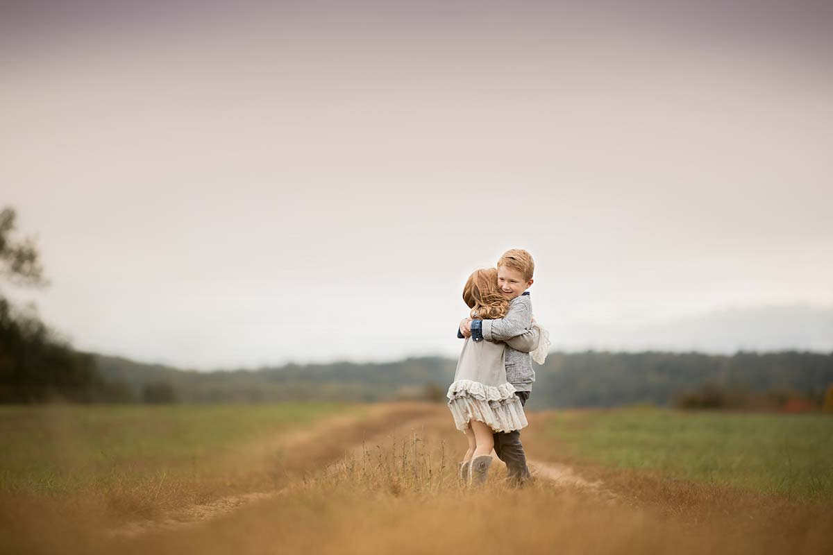 Brother and sister hugging each other on this picturesque farm in Westchester County